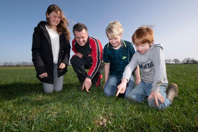 De familie Smets en een kievitsnest in Haghorst. Op de foto wijzen ze het nest aan. Van lnr dochter Caia, vader Martijn Smets en de zonen Krijn en Teye.