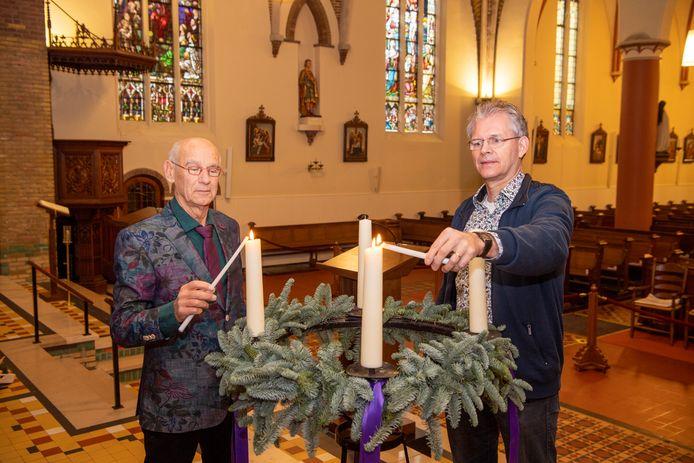 Voorzitter Ben Viskaal (links) en Helmuth Rijnhart van de locatieraad ontsteken kaarsen in de Sint Vituskerk.