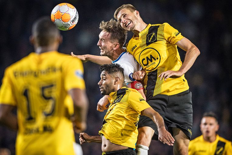 NAC probeert PSV'er Luuk de Jong (m) af te stoppen met Anouar Kali en Karol Mets (r). Beeld Guus Dubbelman / de Volkskrant