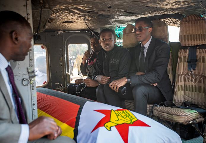 De kist met daarin voormalig president Robert Mugabe's, met naast hem zijn twee zonen Chatunga Mugabe (in het midden) en  Robert Mugabe Junior, rechts.