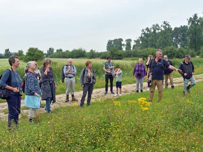 Tijdens de wandeling in de Waterwinbossen ter ere van het 65-jarig bestaan van De Steltkluut heeft gids Guy de Vos (korte broek) veel aandacht voor de invasieve soorten en natuurbeheer.