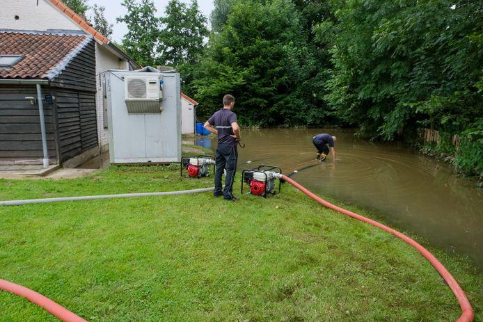 De brandweerdienst pomp de grote plas weg.