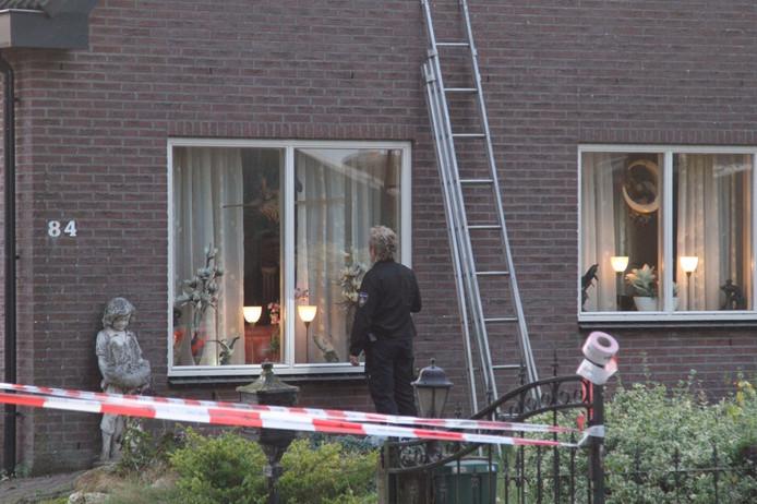 Een agente stelt sporen veilig na de woningoverval aan de Lunterseweg.