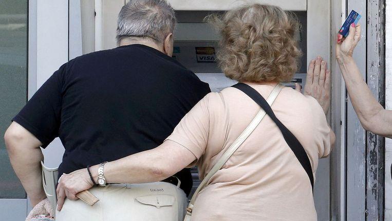 Een heuse run op de banken is voorlopig uitgebleven, al gingen veel Grieken het dagelijkse maximumbedrag van 60 euro afhalen. Beeld © REUTERS