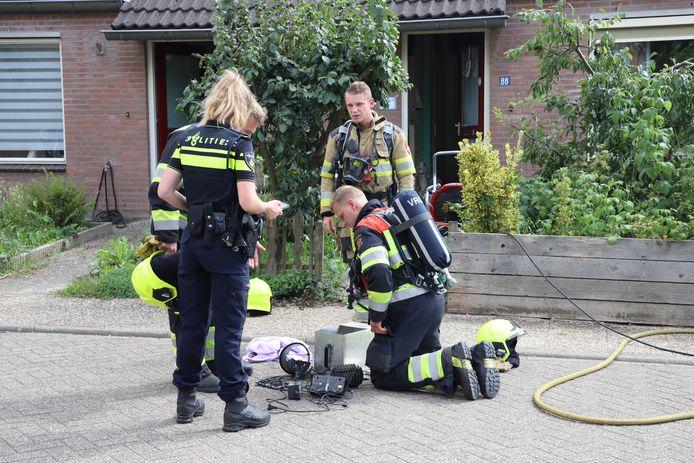 De brandweer bekijkt de mogelijke oorzaak van de brand in de woning in Lienden.