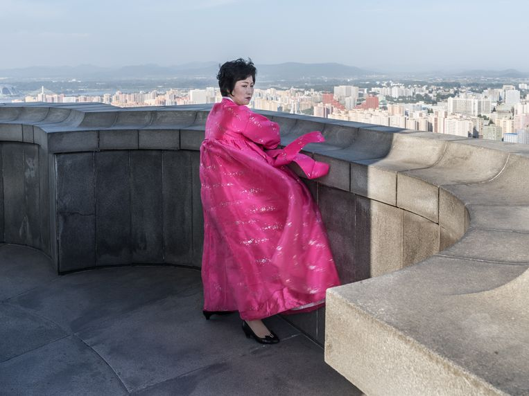 Een lokale gids en kenner van de skyline van Pyongyang in traditionele klederdracht. Beeld Magnum Paris