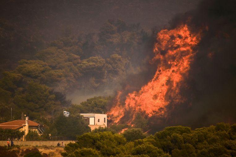 Vlammen vlakbij een huis in het dorp Synterina, bij Athene. Beeld AFP