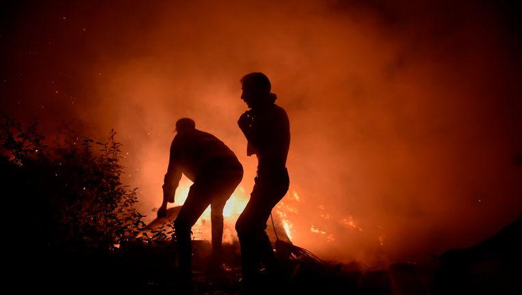 Brandweerlieden en vrijwilligers proberen het vuur in Vigo te bestrijden. Beeld afp
