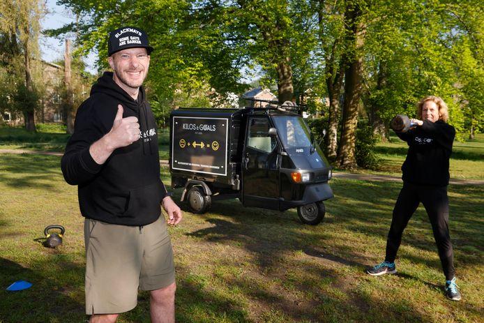 Dennis Gerritzen geeft met zijn tuktuk sportlessen in het Groesbeekse park Mariëndaal. Sporter José Hoogenkamp is druk in de weer met een gewicht.