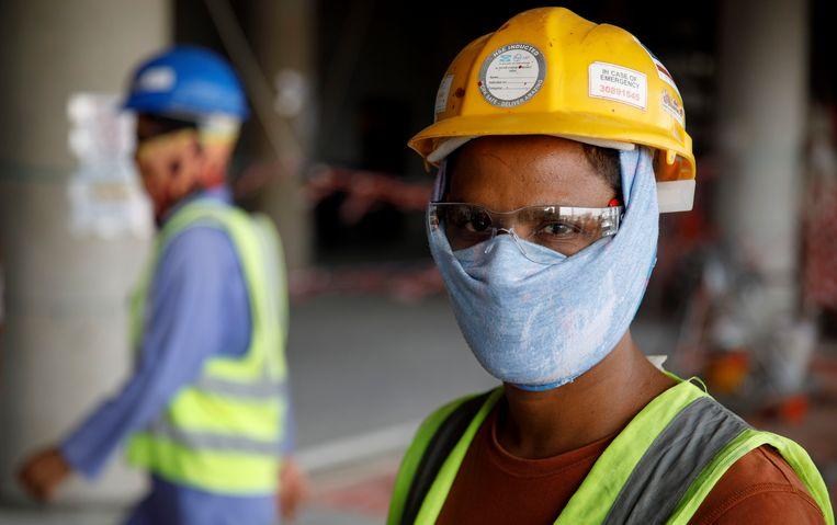Een migrerende werknemer op de bouwplaats voor het Al Rayyan-stadion .  Voor de bouw van