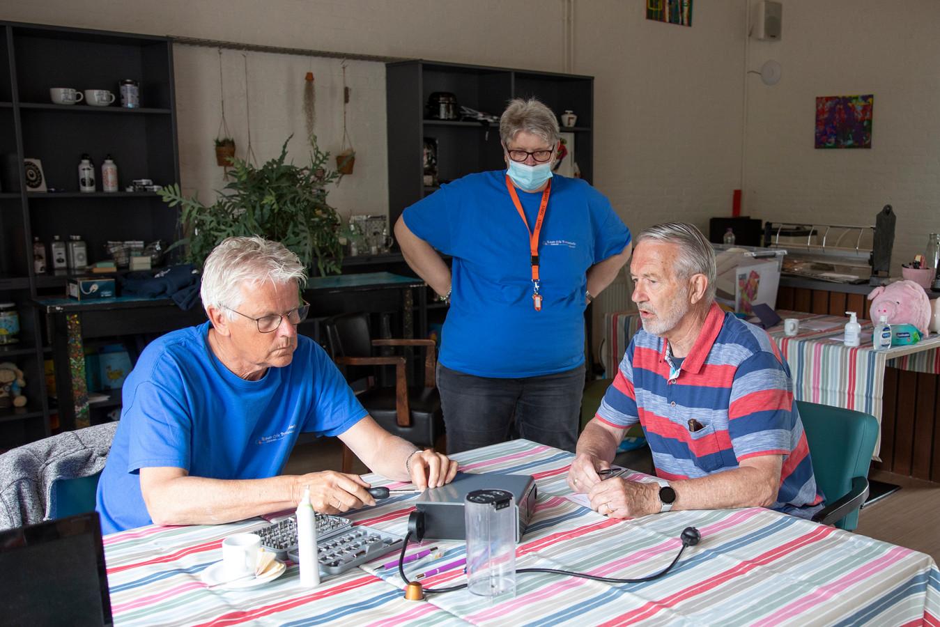 Jan Westerop (rechts) is met zijn koffiezetapparaat naar het repaircafé gekomen. Bas de Vos probeert het eerst maar eens open te maken. Achter kijkt coördinator Marjan van Leeuwen toe.
