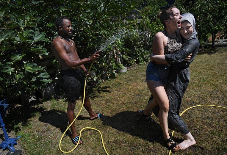 Jongeren spelen in de tuin met water.  Beeld Marcel van den Bergh / de Volkskrant