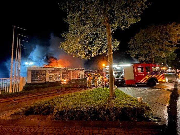 De garage staat in brand; de brandweer probeert te voorkomen dat het vuur ook het kantoorgedeelte bereikt.