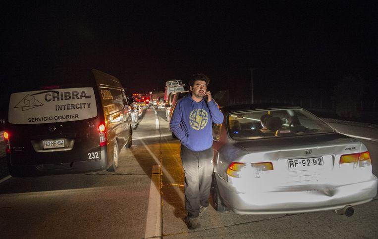 Mensen wachten op de Panamericana snelweg na een sterke aardbeving, 150 kilometer ten noorden van Santiago. Beeld anp