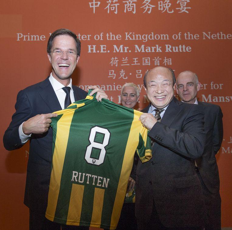 Premier Mark Rutte kijkt naar een shirt van ADO Den Haag met zijn fout gespelde naam erop dat hij kreeg van de nieuwe Chinese eigenaar van ADO Hui Wang. Beeld anp