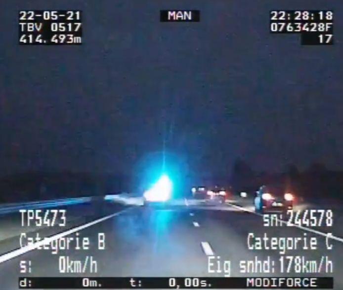 Een politieauto probeert de achtervolgde auto (die op dit beeld op de vluchtstrook een andere auto inhaalt) af te remmen.