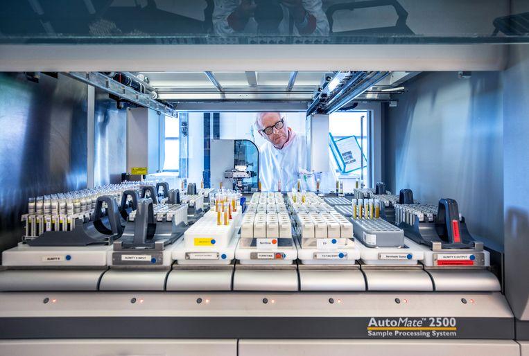 Hans Zaaijer, hoofd van de afdeling Bloedoverdraagbare infectieziekten bij Sanquin. Voor hem een van de machines om corona–antistoffen in het bloed te detecteren. Beeld Raymond Rutting / de Volkskrant