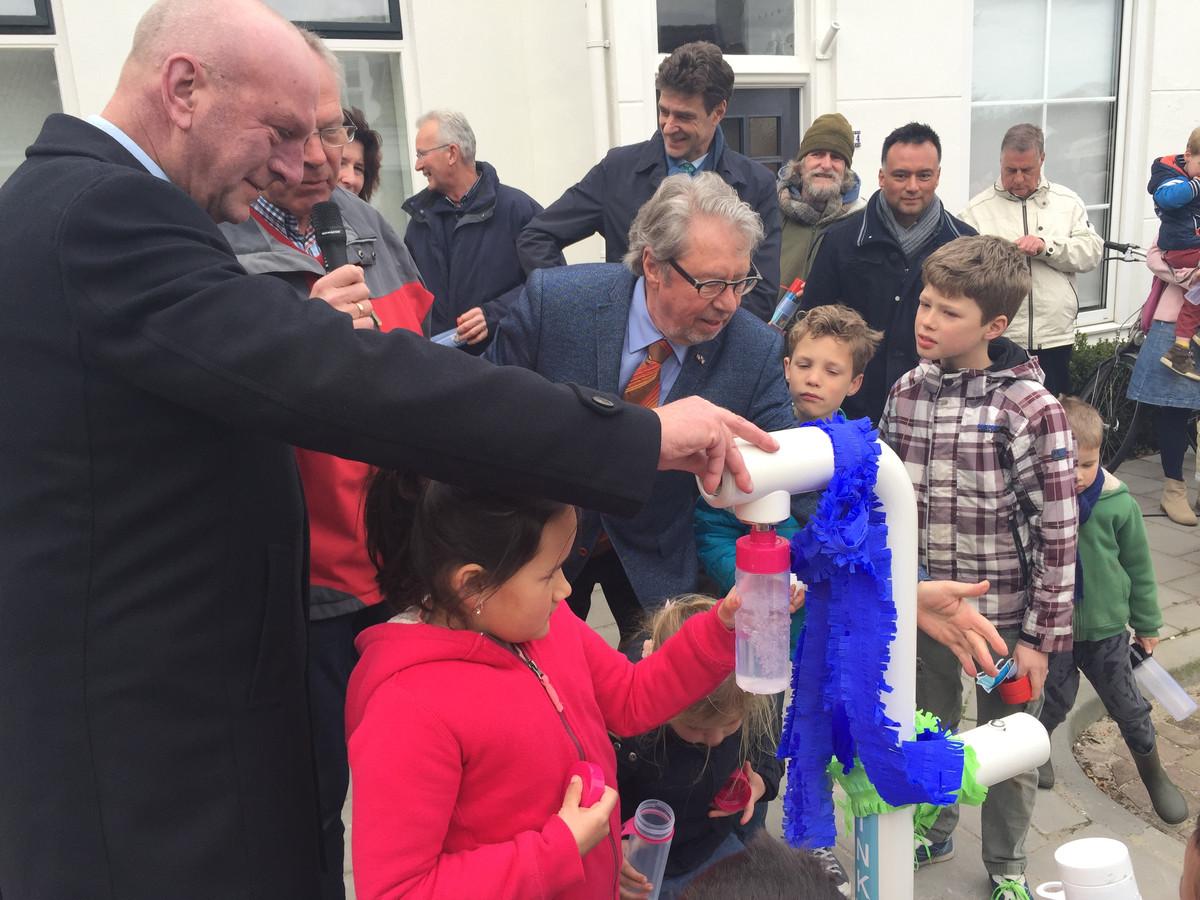 Dijkgraaf Toine Poppelaars van Waterschap Scheldestromen (links) en Bram Rodenburg van wijkteam 't Zand-Stromenwijk (oranje-rode stropdas) helpen kinderen met het vullen van flessen bij het gratis watertappunt van het project Join the pipe, in de Burgemeester Dregmanstraat.