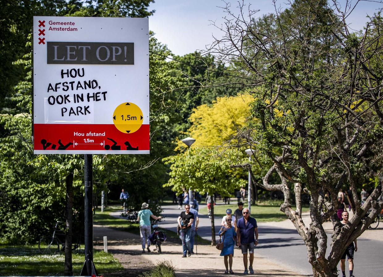 In het Amsterdamse Vondelpark wijzen borden de bezoekers op de coronamaatregelen.  Beeld EPA