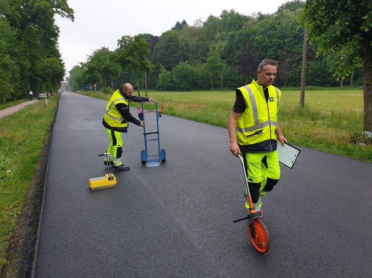 Medewerkers van AWV testen de kwaliteit van het 'groene' asfalt dat als proefvak werd aangelegd in de Kasteelstraat in Retie.