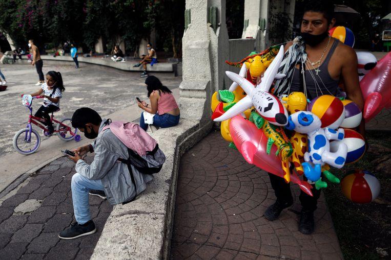 Een man verkoopt balonnen in Parque Mexico, in Mexico-Stad. De pandemie lijkt er af te vlakken. Beeld AP
