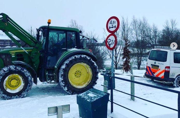 Een boer trekt met zijn tractor in Ooij een politiebusje uit de sneeuw.