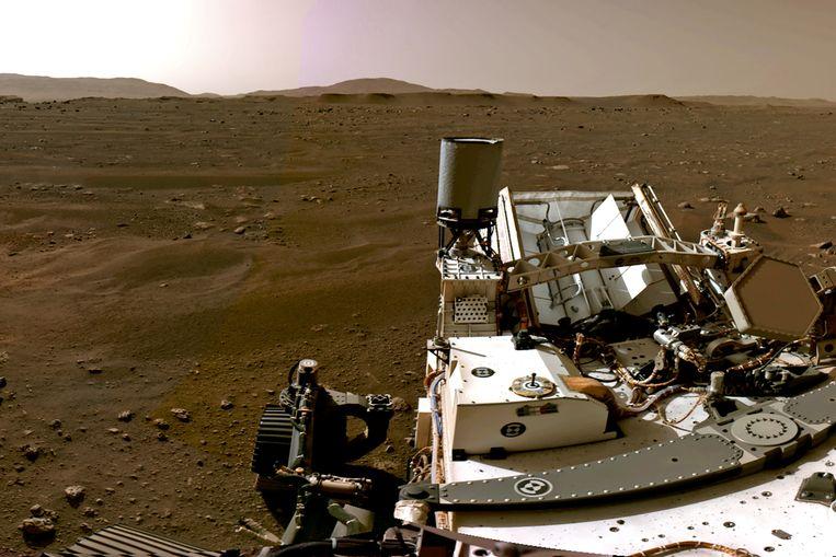Panoramafoto van Perseverance, gemaakt met de eigen navigatiecamera's, na het ontwaken op zijn nieuwe thuisplaneet.   Beeld REUTERS/NASA/JPL-Caltech