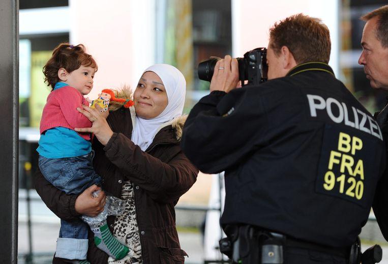 Een moeder en haar baby worden gefotografeerd tijdens de registratie bij hun aankomst in de Duitse stad Freilassing. Ze reisden per trein van Oostenrijk naar Duitsland.