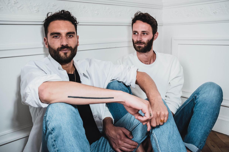 Hugues (links) en Kenny hebben maar één kleerkast in hun Brusselse woonst.Ieder item is gemeengoed. Beeld David Rodrigues