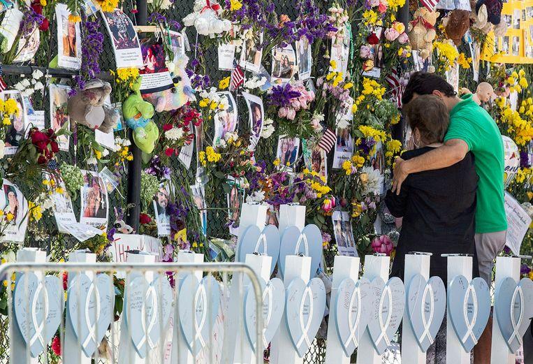 Bij het ingestorte flatgebouw in Miami is een herdenkingsmuur geplaatst, vol foto's en bloemen voor de slachtoffers.  Beeld AP