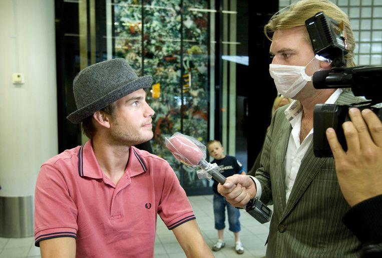 Verslaggever Rutger Castricum van website Geenstijl.nl doet woensdag, voorzien van een mondkapje, in de aankomsthal van Schiphol verslag over de varkensgriep. Foto ANP/Evert Elzinga Beeld