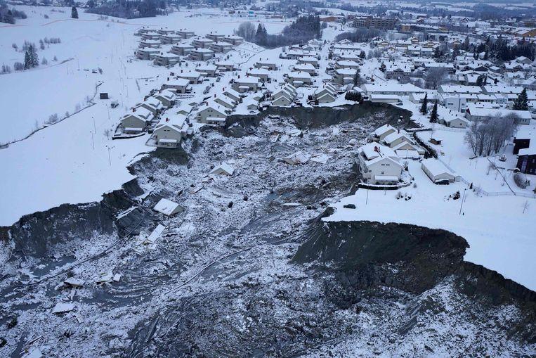 Het lijkt alsof er een enorme schaduw over het Noorse Ask hangt, en dat is ook zo, maar de werkelijkheid is nog veel erger. Deze luchtfoto toont de aardverschuiving van 30 december die inmiddels aan zeven inwoners het leven heeft gekost. Er zijn nog drie vermisten, maar de Noorse politie zei deze week dat er geen hoop is dat zij levend worden gevonden. Beeld AFP