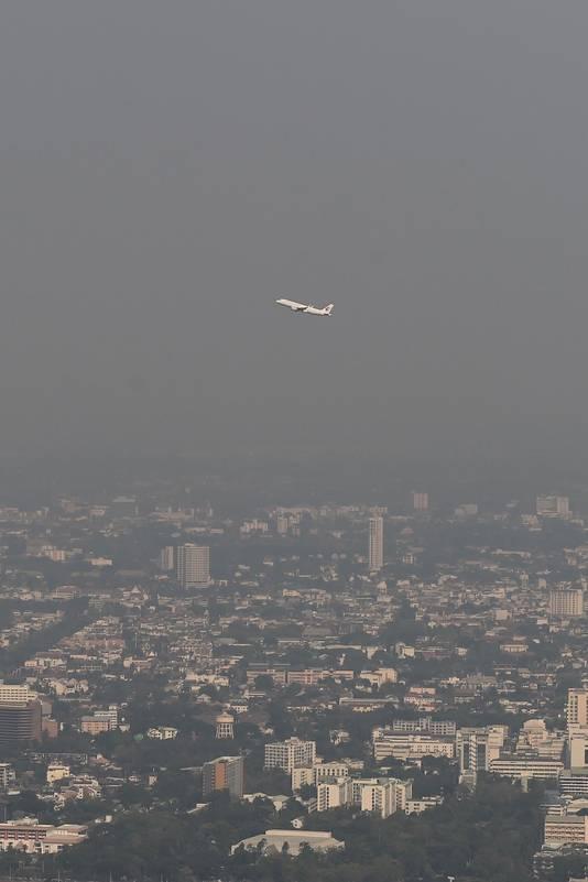 Een vliegtuig vliegt over de met smog bedekte stad in de noordelijke Thaise provincie Chiang Mai.