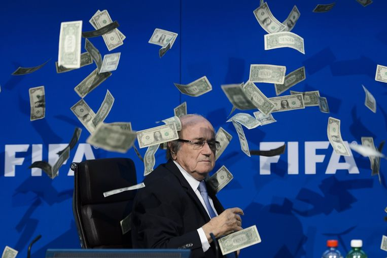 A protester threw fake dollar bills at Sepp Blatter during a press conference at the FIFA headquarters on July 20th, 2015. Beeld ANP