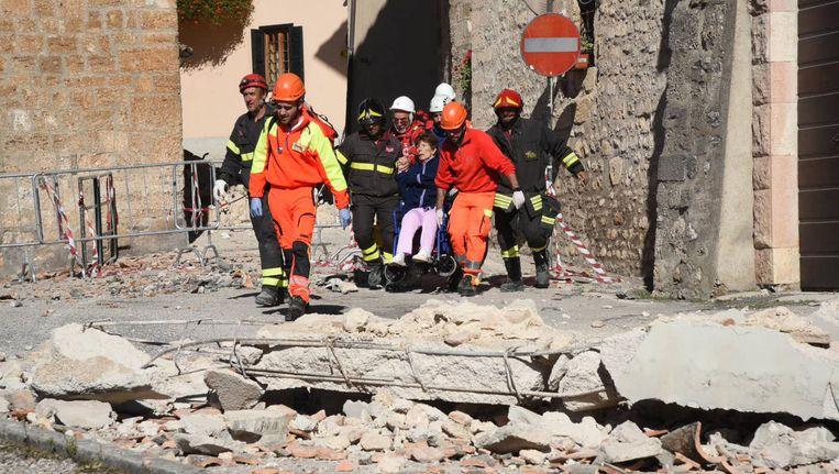 Een inwoner van Norcia wordt geholpen na de aardbeving. Beeld EPA