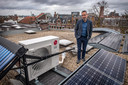 Jan van der Meer bij de buiteninstallatie van z'n warmtepomp, omringd door zonnepanelen en een zonnecollector.