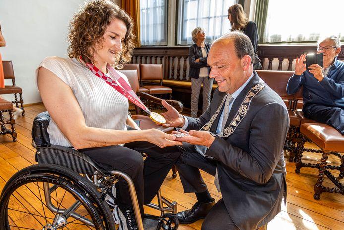 Jitske Visser kreeg uit handen van burgemeester Peter Snijders van Zwolle een koninklijke onderscheiding voor haar topprestatie als rolstoelbasketbalster in Tokyo. Nadien bewonderde hij haar gouden medaille en zij zijn ambtsketen.