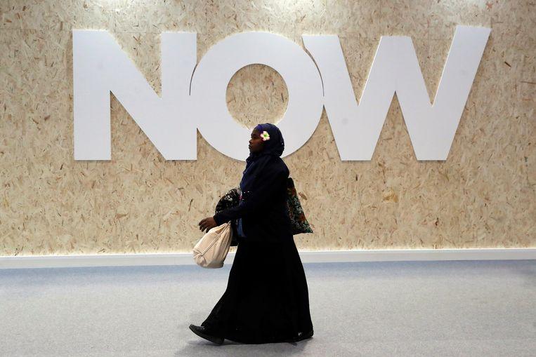 Een van de deelnemers van de Klimaattop passeert een muur met de tekst Now. Beeld EPA