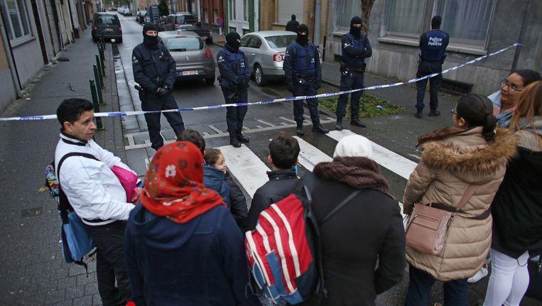 Bewoners van een straat in Molenbeek moesten wachten tot de politie klaar was met het onderzoek. Beeld Ton Koene