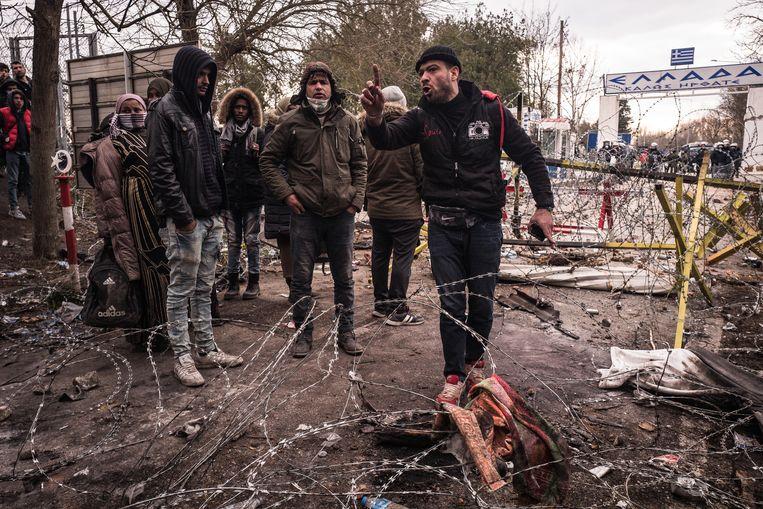 Vluchtelingen bij de Griekse grensovergang. Op de achtergrond de oproerpolitie. Beeld Nicola Zolin