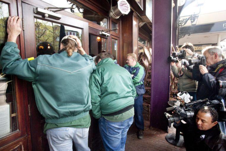 Café The Thtree Sisters aan het Rembrandtplein. Er wordt een nieuw slot in de deur gedraaid. De klusjesman wil niet in beeld en wordt afgeschermd door zijn collega's. Foto Klaas Fopma Beeld