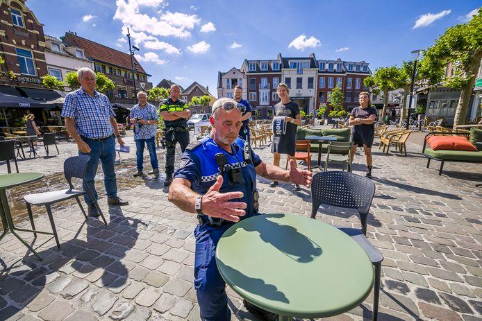 Cor, coordinator handhaving in Boxtel, schetst aan een terrastafel de situatie voor de coronamaatregelen.
