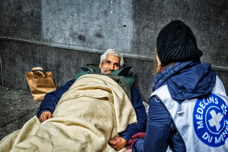 Een medewerkster van Médecins du Monde probeert uit te vissen welke hulp deze dakloze man het meest dringend nodig heeft. Beeld Tim Dirven