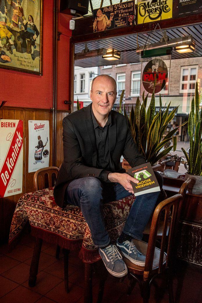 Martijn Jas met zijn roman 'Mooie Vrienden' in De Beyerd, het stamcafé dat in zijn semi-autobiografische boek een belangrijke rol speelt.