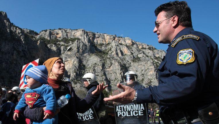Een Griekse politieman luistert naar smeekbedes van een vluchteling met een baby. Door de verscherpte controles aan de Grieks-Macedonische grens zijn er al duizenden migranten in Griekenland gestrand. Beeld ap