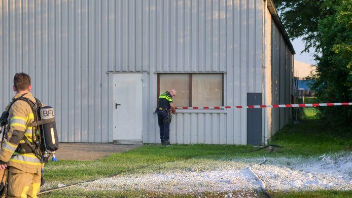 Een politieagent maakt een plaats-delict nadat de brandweer het brandje in het bedrijfspand heeft geblust.