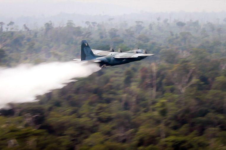 Hercules C-130 dropt water boven de Amazone. Beeld EPA
