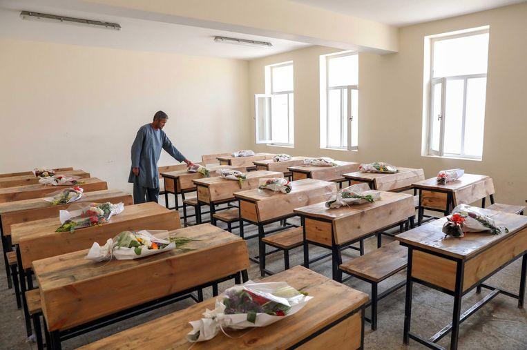Bloemboeketten op lege bureaus ter ere van de slachtoffers van de Sayed ul-Shuhoda High School. Vlak bij die school ligt het gezondheidscentrum van Moeders voor Vrede.  Beeld EPA