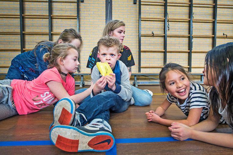 Kinderen van een lagere school ontfermen zich over een zwaar gehandicapte jongen die bij hun in de klas zit. Beeld Guus Dubbelman/ de Volkskrant