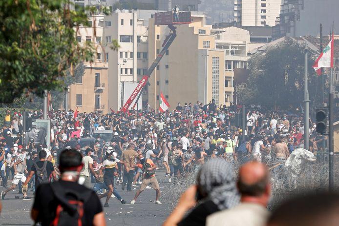 Demonstranten gooien stenen naar de politie in Beiroet, zaterdagmiddag.